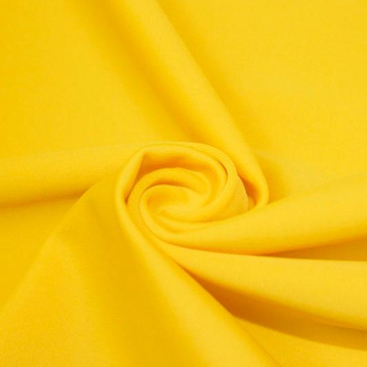 A swirled piece of matte nylon spandex fabric in the color mustard.