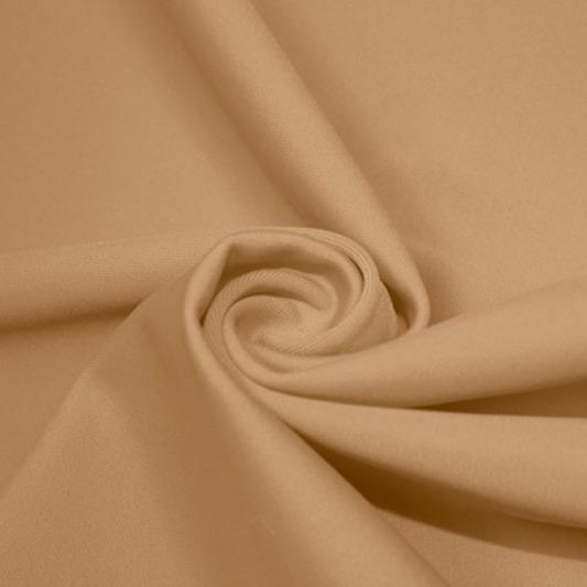 A swirled piece of matte nylon spandex fabric in the color nude.
