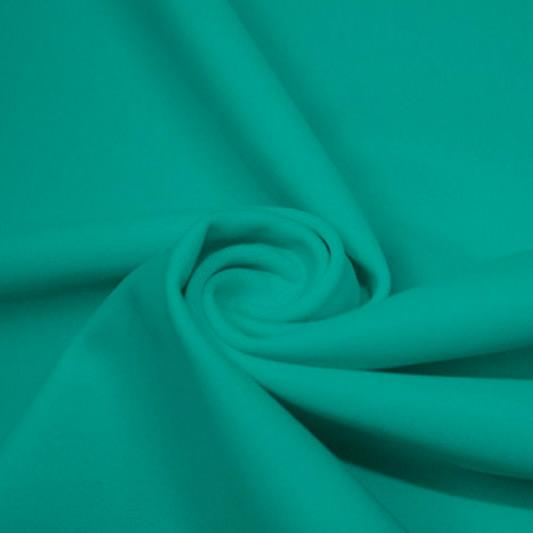 A swirled piece of matte nylon spandex fabric in the color ocean.