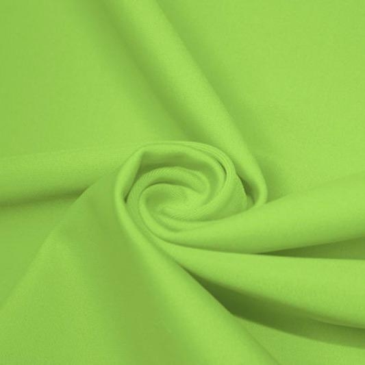 A swirled piece of matte nylon spandex fabric in the color pear.