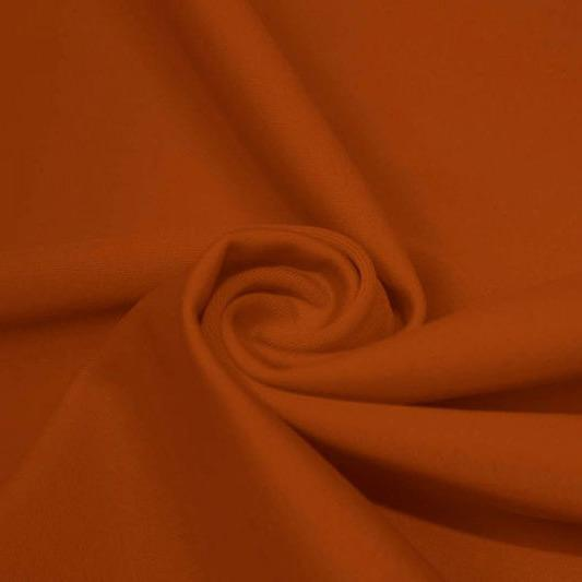 A swirled piece of matte nylon spandex fabric in the color penny.