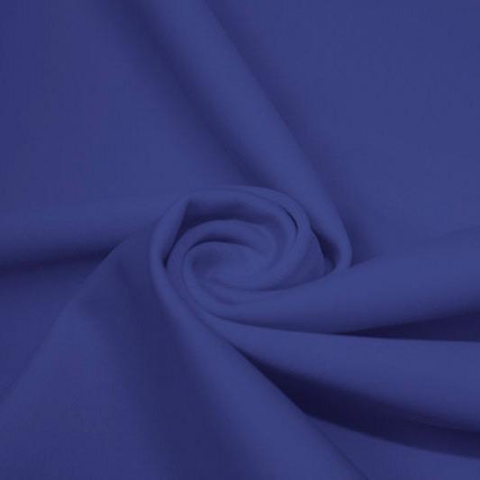A swirled piece of matte nylon spandex fabric in the color real royal blue.
