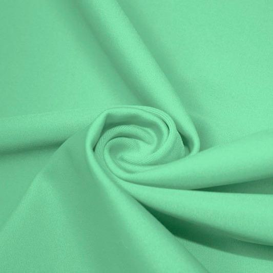 A swirled piece of matte nylon spandex fabric in the color sea foam.