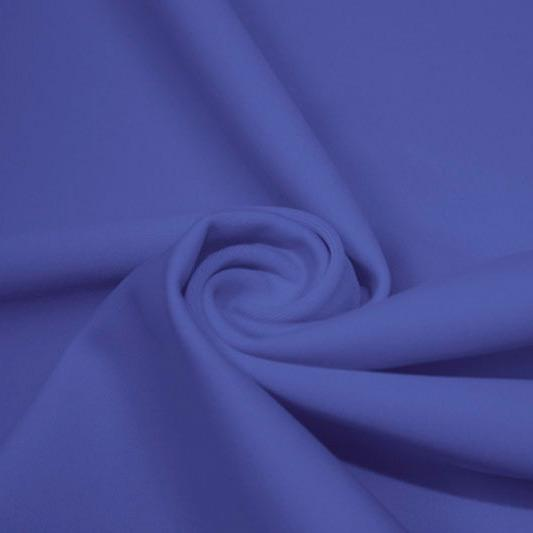 A swirled piece of matte nylon spandex fabric in the color sedona blue.