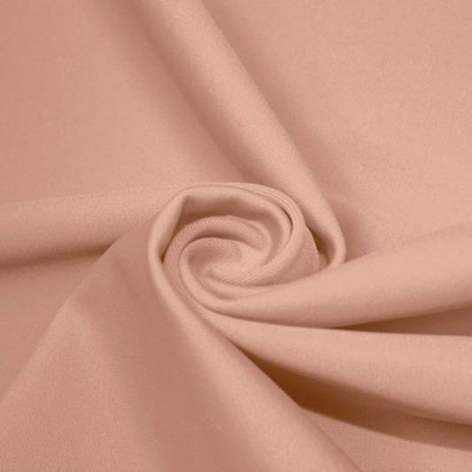 A swirled piece of matte nylon spandex fabric in the color sun beige.