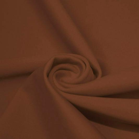 A swirled piece of matte nylon spandex fabric in the color sweet syrup.