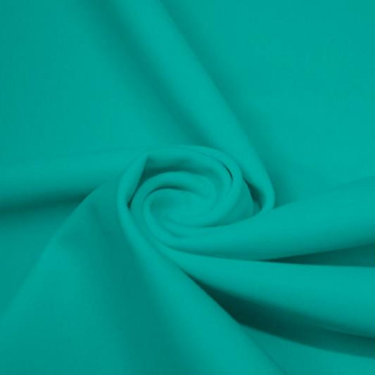 A swirled piece of matte nylon spandex fabric in the color teal.