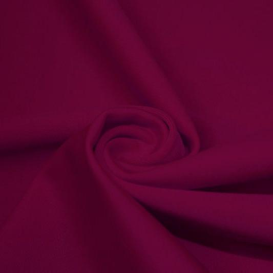 A swirled piece of matte nylon spandex fabric in the color wine.