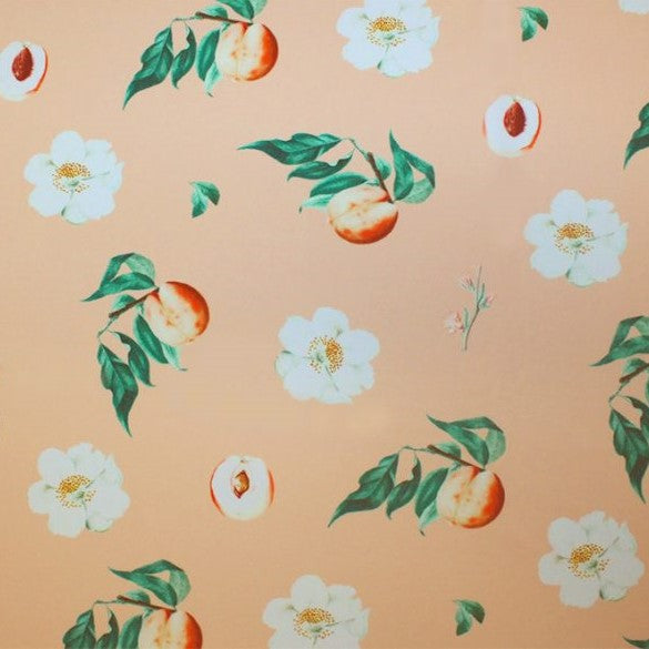 A flat sample of peaches and cream printed spandex.