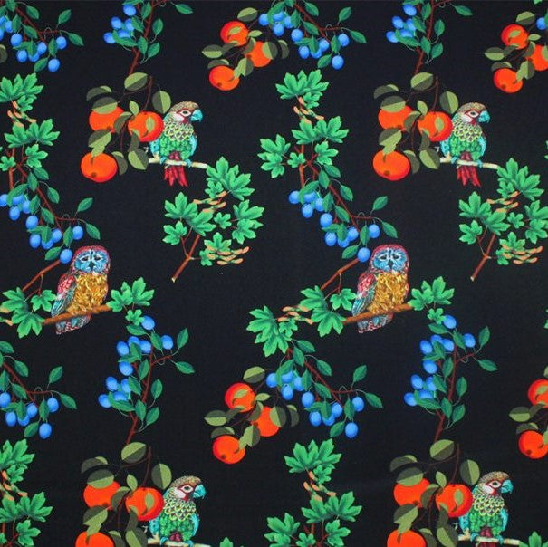 A flat sample of birds and fruit printed spandex.