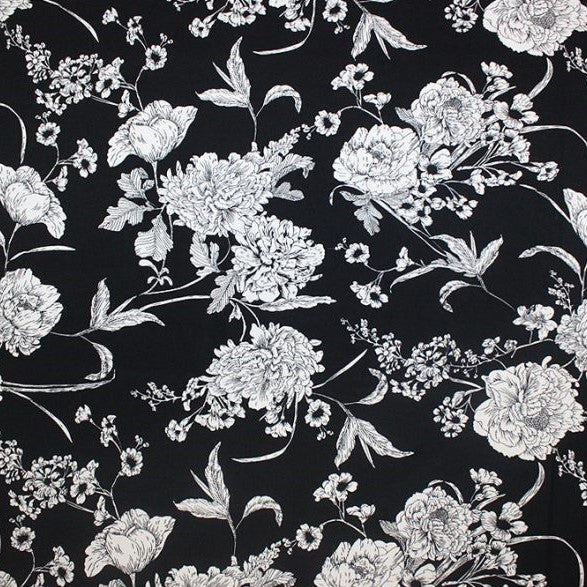A flat sample of white flowers on black printed spandex.