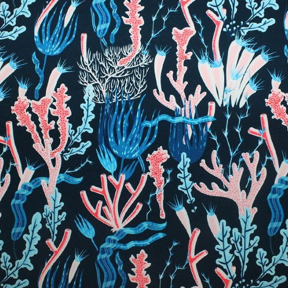 A flat sample of coral reef on navy printed spandex.