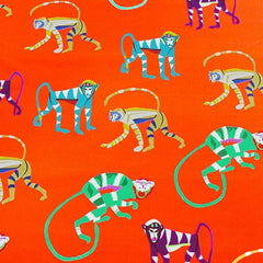 A flat sample of orange monkey printed spandex.