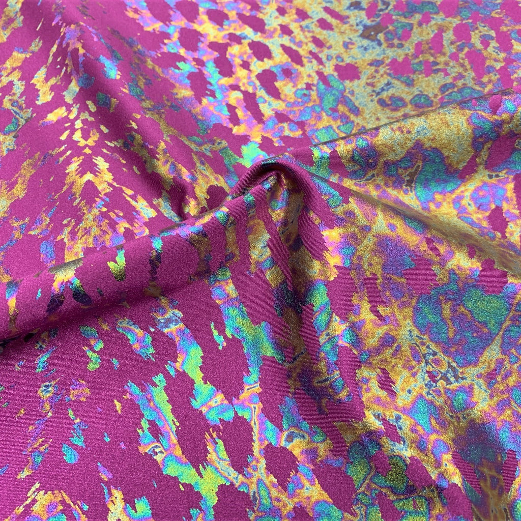 A swirled sample of naga foil printed spandex in the color mulberry/iridescent.