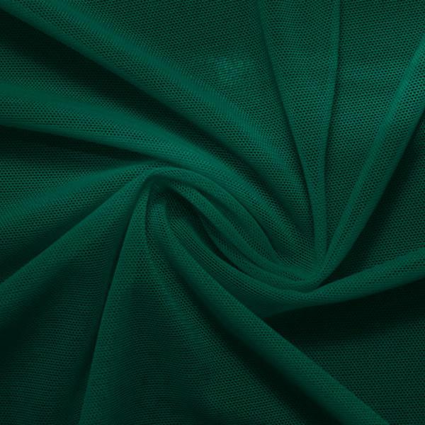 A swirled piece of nylon spandex power mesh in the color alpine green.