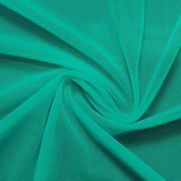 A swirled piece of nylon spandex power mesh in the color aqua tides.