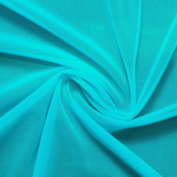 A swirled piece of nylon spandex power mesh in the color light turquoise.