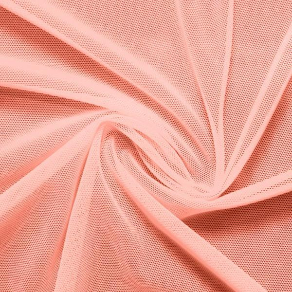 A swirled piece of nylon spandex power mesh in the color salmon.
