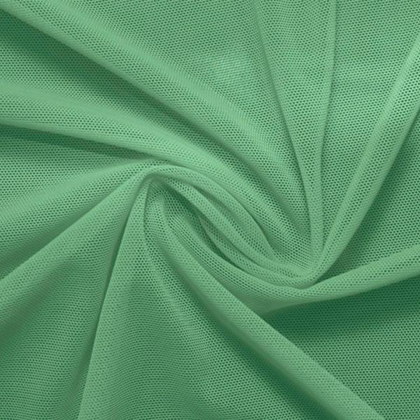 A swirled piece of nylon spandex power mesh in the color sea foam.