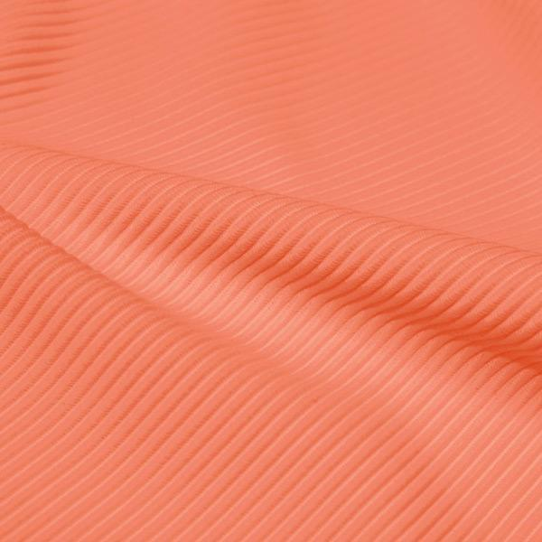 A rippled piece of Ribbed Spandex in the color cantaloupe.