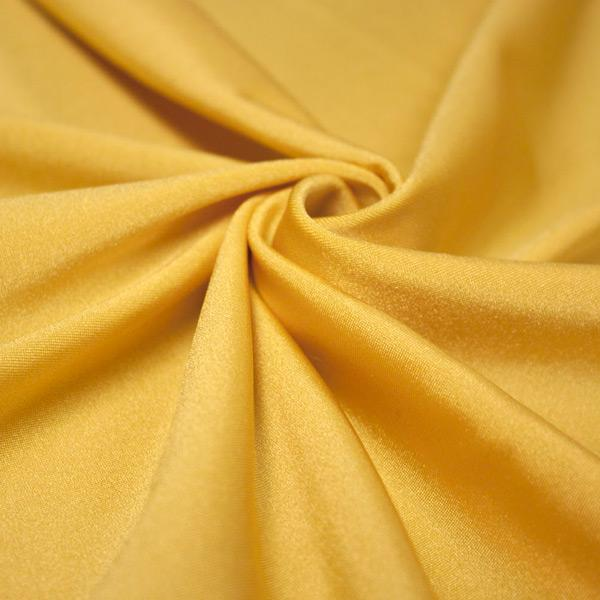 A swirled piece of shiny nylon spandex in gold.