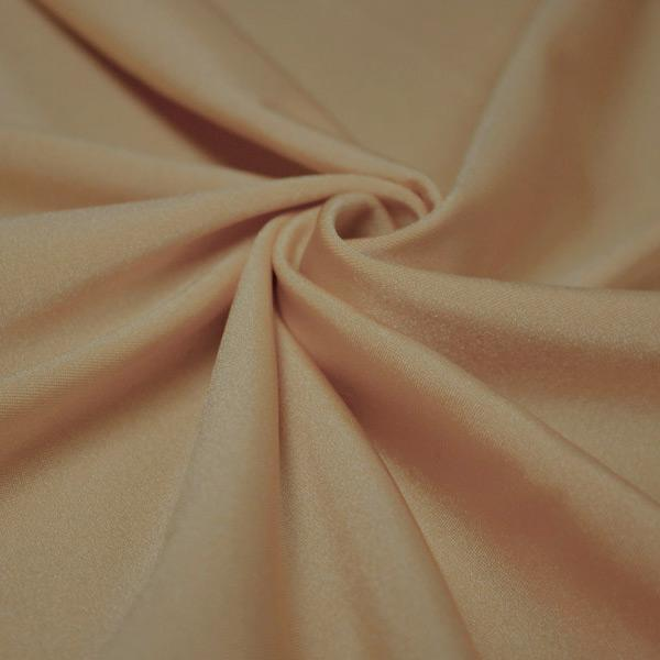 A swirled piece of shiny nylon spandex in latte.