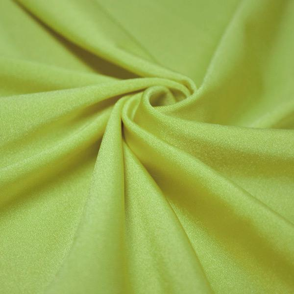 A swirled piece of shiny nylon spandex in lime.