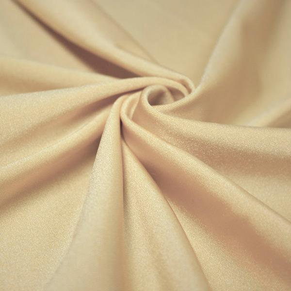 A swirled piece of shiny nylon spandex in nude.