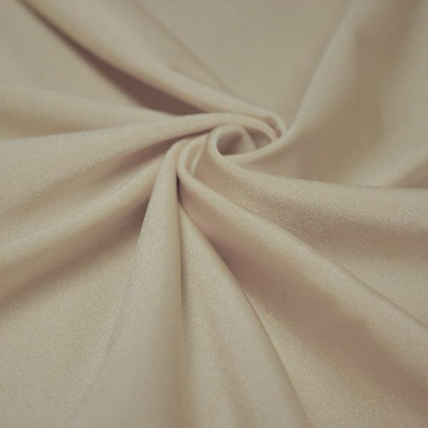 A swirled piece of shiny nylon spandex in taupe.