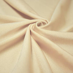 A swirled piece of shiny nylon spandex in wheat.