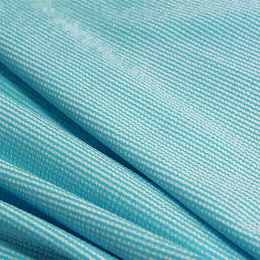 A rippled piece of stretch seersucker material in the color celeste blue.