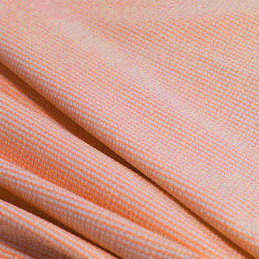 A rippled piece of stretch seersucker material in the color coral.
