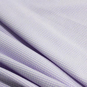 A rippled piece of stretch seersucker material in the color lilac.