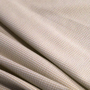 A rippled piece of stretch seersucker material in the color taupe.