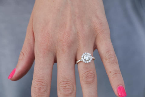 Custom engagement ring featuring a round center stone diamond with .75cttw round diamond halo and shank.