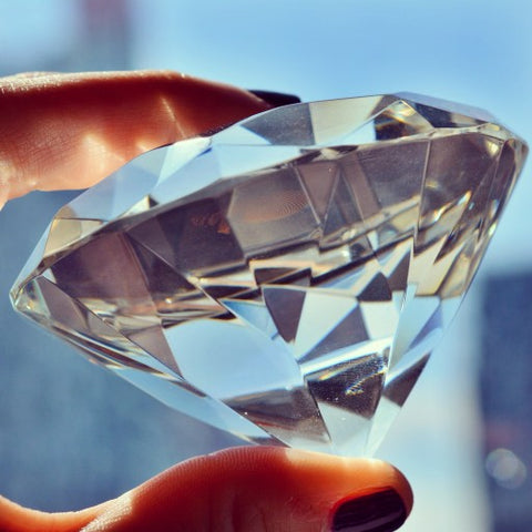 Close up of woman holding diamond between her fingers