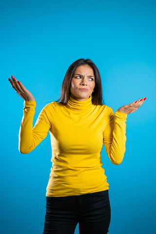 Woman standing shrugging shoulders in front of blue backdrop