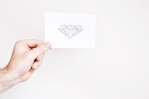 Hand holding a paper with drawing of diamond