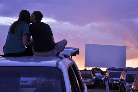 Man kissing woman on cheek while on top of car watching drive in movie