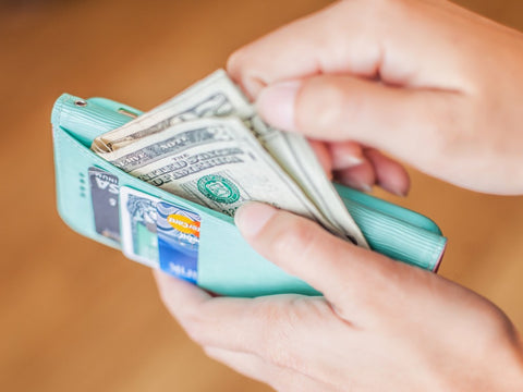 Hand pulling money out of little blue wallet