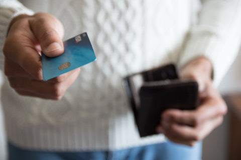 Man with open wallet holding card out