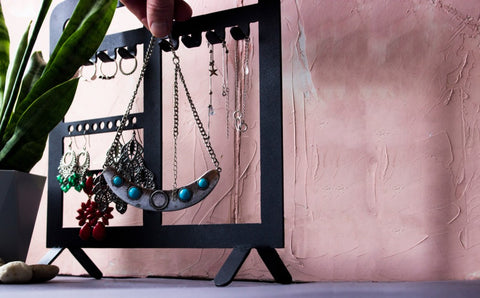 Jewelry such as necklaces and earrings hanging from black jewelry stand