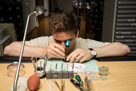 Man with magnified glass tool on eye fixing jewelry