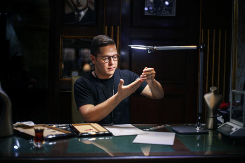 Jeweler examining a necklace in a dark room under a light at his desk
