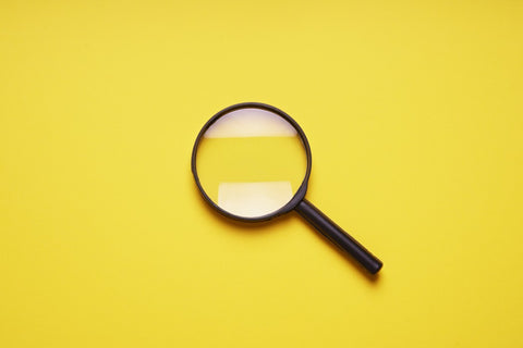 Magnifying glass in front of yellow backdrop