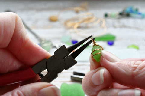 Person using round nose pliers making jewelry