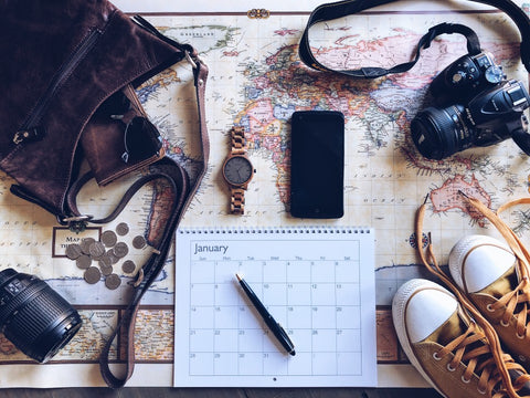 Travel essentials such as shoes, watch, phone, etc on map