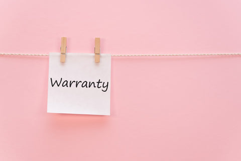 """""""warranty"""" written on paper clipped to string"""
