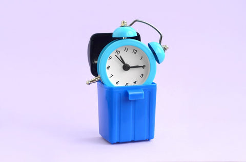Blue old fashioned alarm clock sticking out of tiny blue garbage can