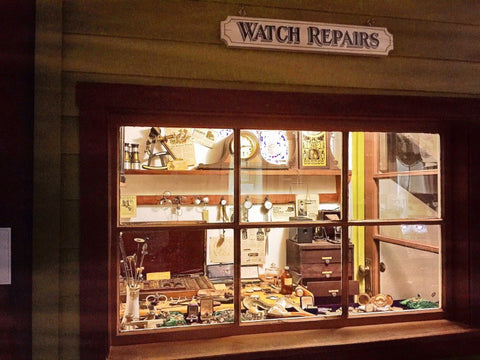 Watch Repairs shop lit up with desks and watch pieces